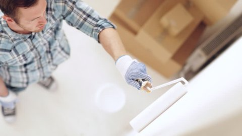 footage of man painting with white paint