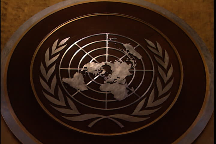 NEW YORK CITY - FEBRUARY 11, 1999: Zoom in to ECU the United Nations Emblem in silver on the wall of the United Nations General Assembly hall