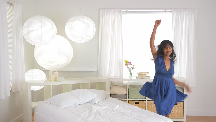African American girl dancing and jumping on bed