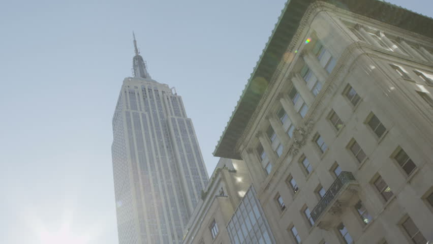 Low angle view of the Empire State Building and the surrounding buildings on a bright sunny day in New York City.