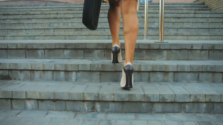 Filmed feet only young business woman walking to the office and back. She climbs the stairs to the office building, and then back down. static camera shoots. Odessa, Ukraine
