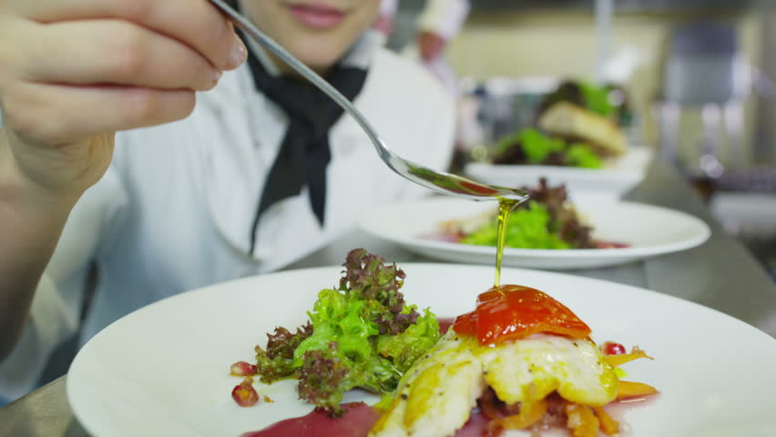 A delicious gourmet meal is being given the finishing touches by the chef in a restaurant or hotel kitchen, ready for service to the customer.