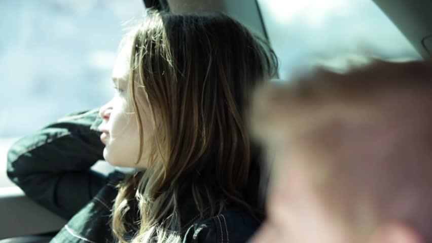 Older sister in the car backseat enjoying the landscape
