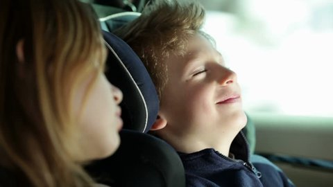 Kids in the backseat of car playing a game of sleeping