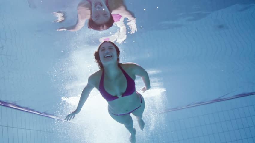 Beautiful woman in a pink bikini diving in and swimming underwater.