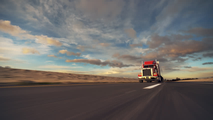 18 Wheel Truck on the road with sunset in the background. Large delivery truck is moving towards setting sun.