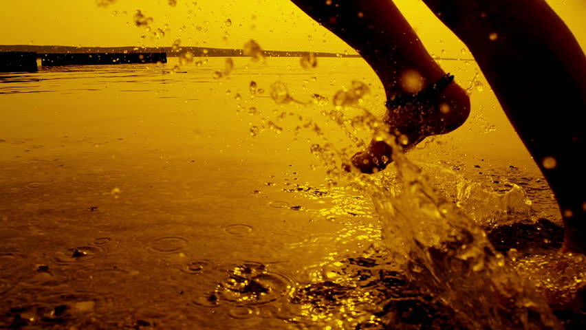 SLOW MOTION: Girl running in shallow water at sunset #4465301