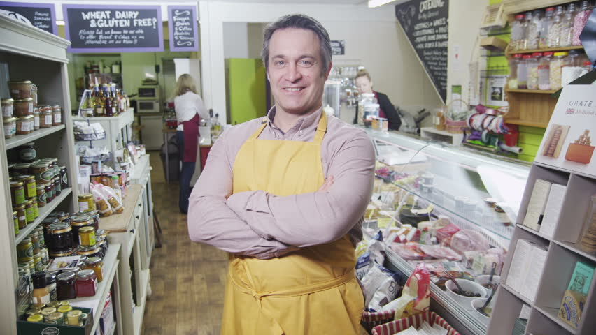 Portrait of a happy and successful male shopkeeper in a delicatessen or food store. Members of his staff can be seen working in the background.