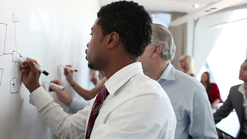 Business people brainstorming ideas on a whiteboard in a large corporate office. Attractive workers building a plan together. A teamwork scene with lovely DOF. High quality HD video footage | Shutterstock HD Video #4493381