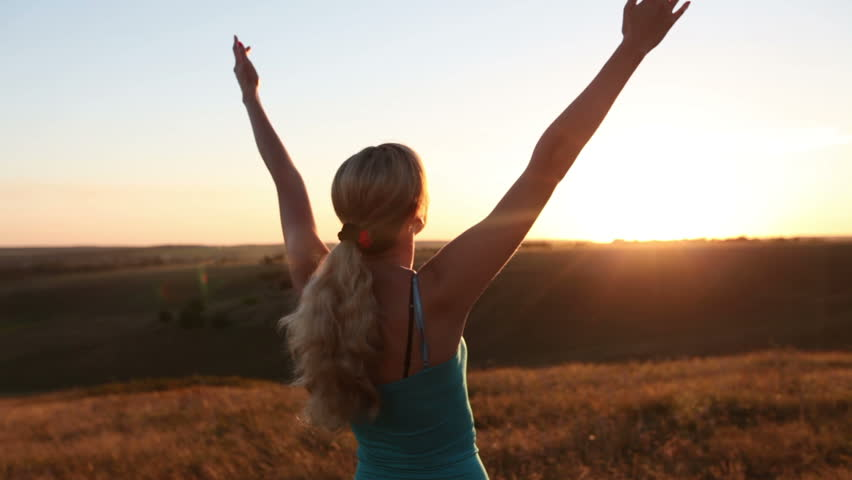 Blonde girl raising arms to sunset summer sky. Girl relaxing and enjoying nature.
