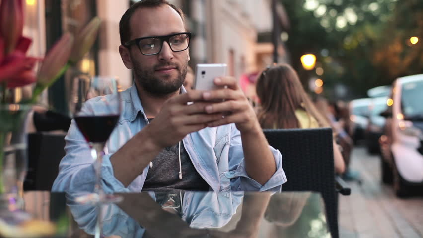 Happy man with smartphone drinking wine in cafe