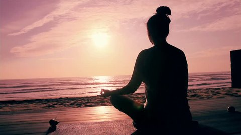 Meditation near the sea & doing yoga on a beach at sunrise