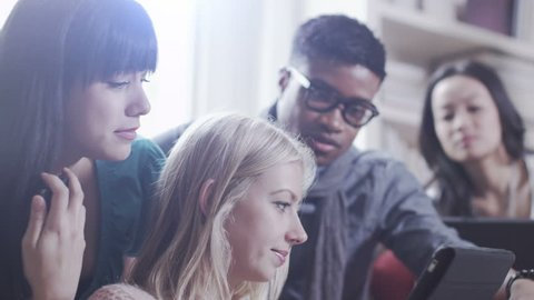 Student house accommodation. Flat share with teenagers or young adults using digital tablet.