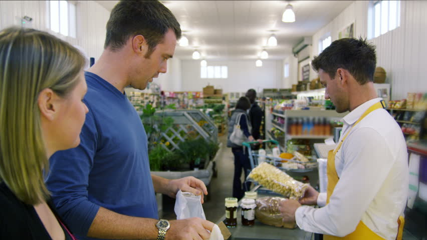 Customers buying food and staples from a cashier and paying at the till. Supermarket store. | Shutterstock HD Video #4501466