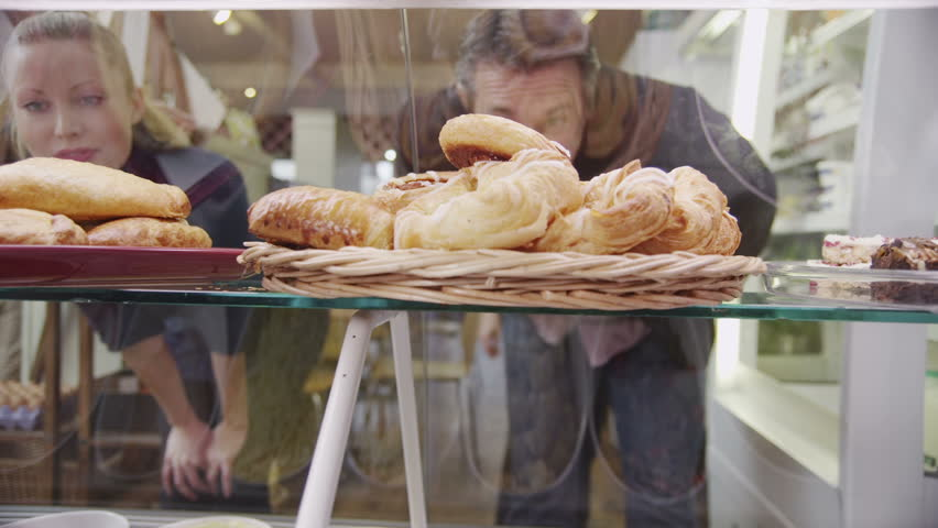 Happy customers looking through the glass and choosing fresh pastries at the bakery counter. In slow motion. | Shutterstock HD Video #4506611