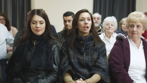 Group of various people sitting in the audience at a community or political meeting. One woman shares an opinion.