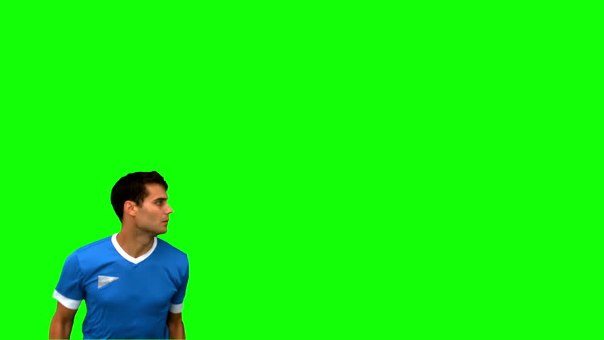Attractive man heading a football on green screen in slow motion
