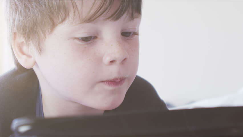 Young boy using touchscreen tablet technology and reading. | Shutterstock HD Video #4532816