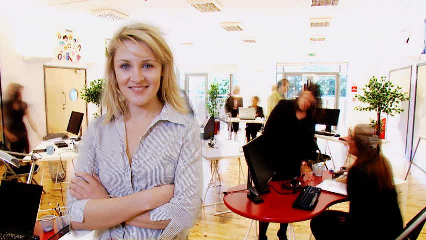 Confident business team working together in modern office. Time lapse of busy office behind blonde young boss.
