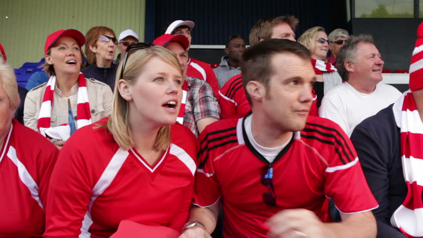Enthusiastic crowd of spectators watching a sports game or football match and reacting  | Shutterstock HD Video #4536248