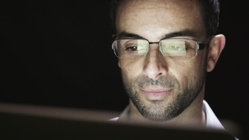 Close up of young man reading his tablet in the dark. Black background.  | Shutterstock HD Video #4536809