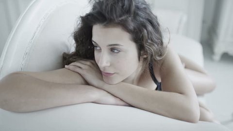 Beautiful brunette model in black lingerie laying across a white chaise longue and relaxing in her elegant boudoir.
