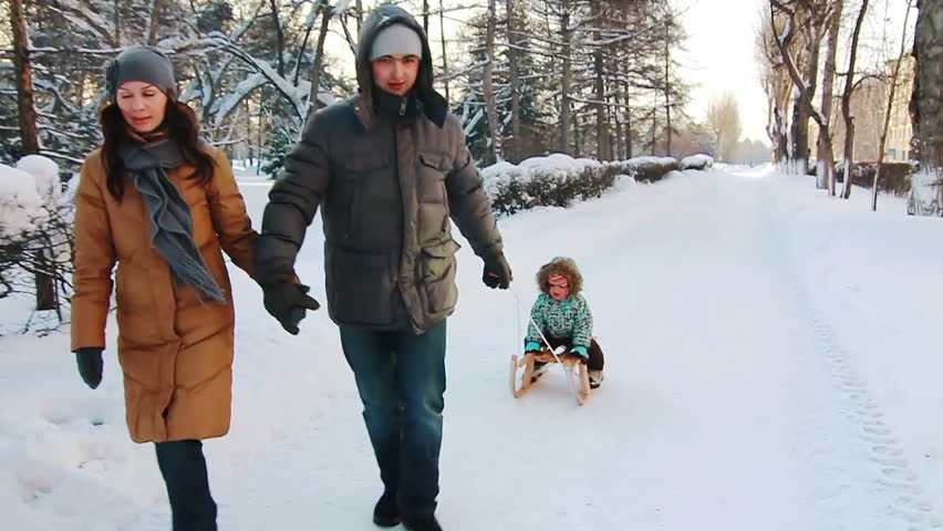 Parents are holding hands and sledging his son along the road. Park in winter.