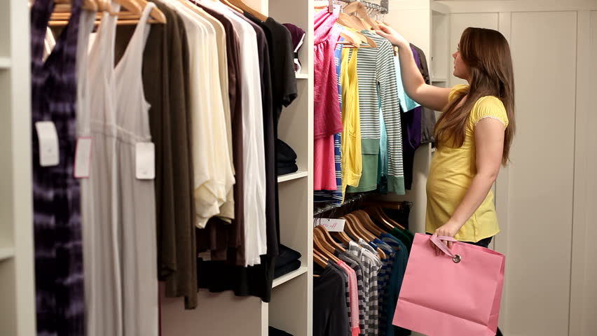 Young girl looks at clothing in store