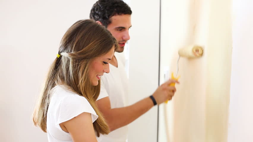 Young couple decorate their new apartment.They are painting the wall.