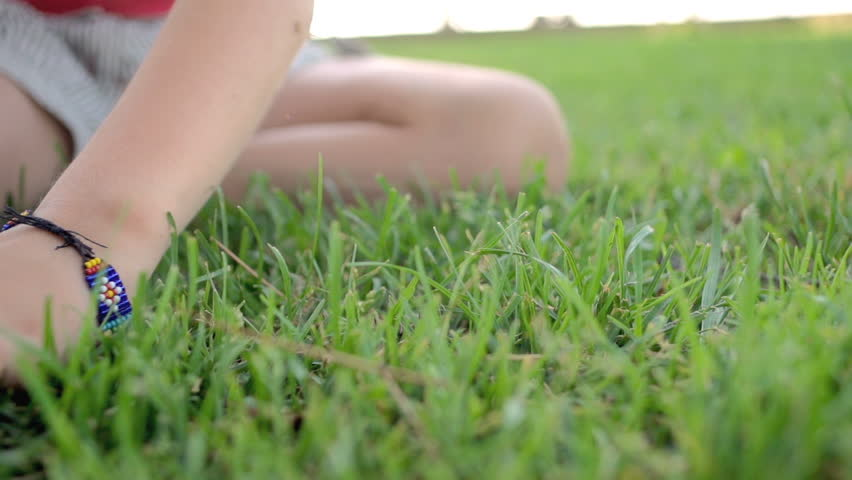 Slow Motion Shot Of A Little Girl's Hand Gently Caressing Green Grass