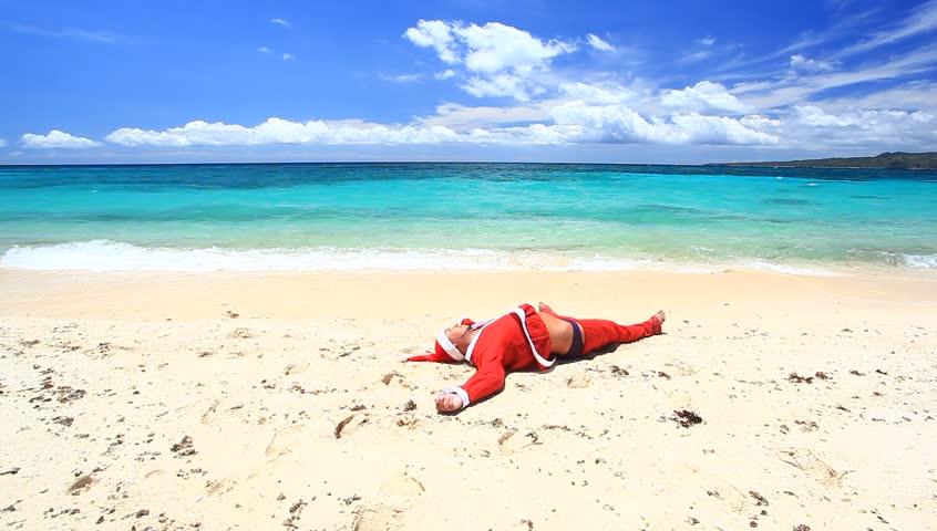 Santa claus jumps on tropical beach, caribbean christmas