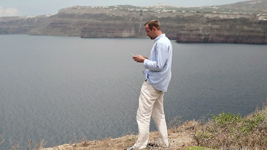 Young man using smartphone by the sea