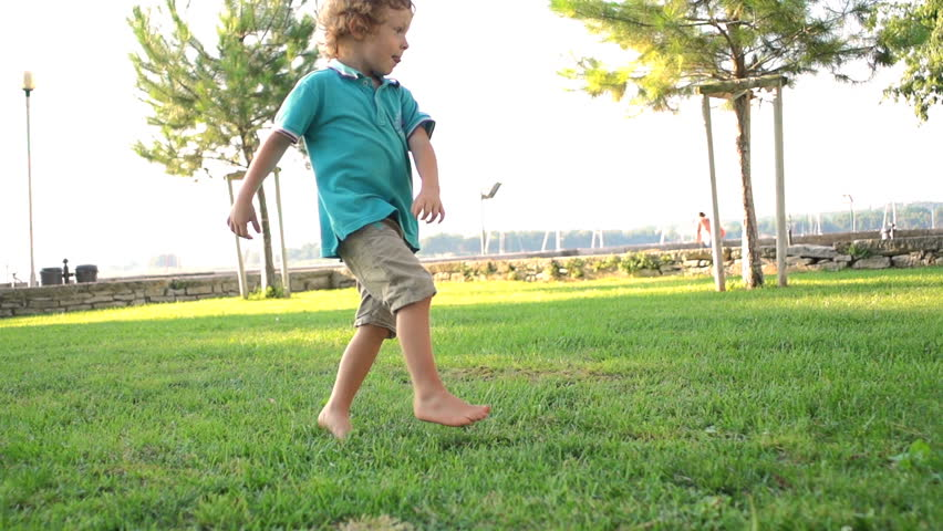 Slow Motion Shot Of A Cute Three-Year-Old Boy Skillfully Kicking A Football Ball