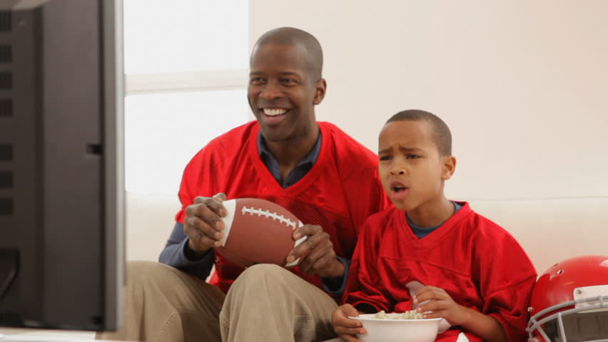 Father and son watching football game on TV