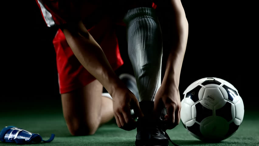 Soccer player puts on shin pads, preparing to play. Close up shot