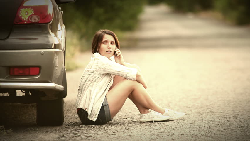 Pretty girl talking by phone after car incident