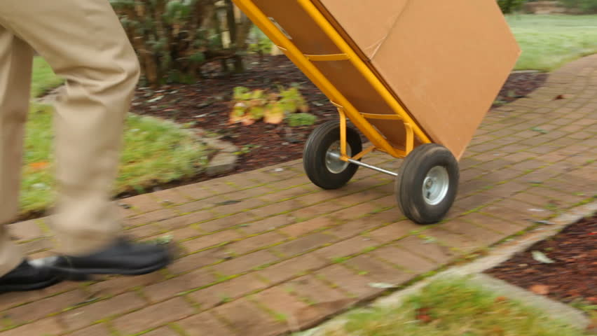Delivery man pushes dolly full of packages to home