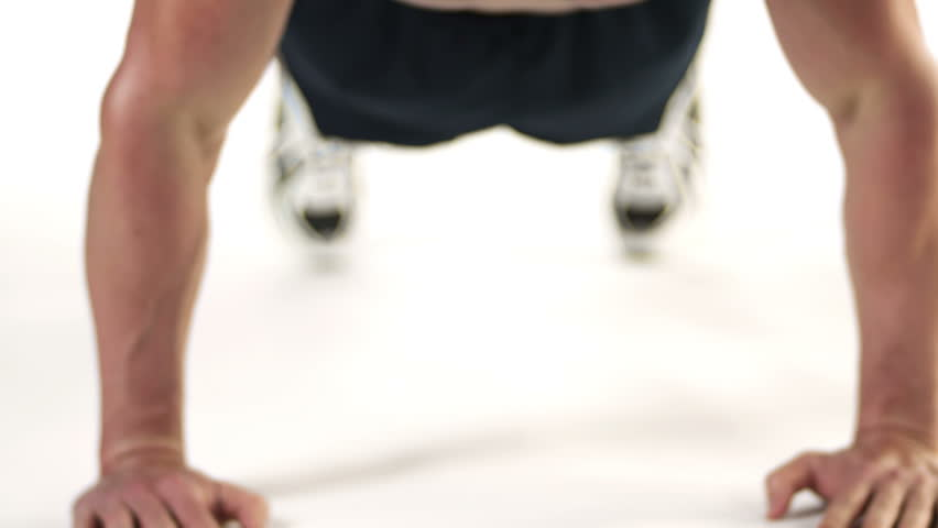 Close up shot of a muscular bodybuilder doing push ups and looking into the camera on a white background, with a camera pan