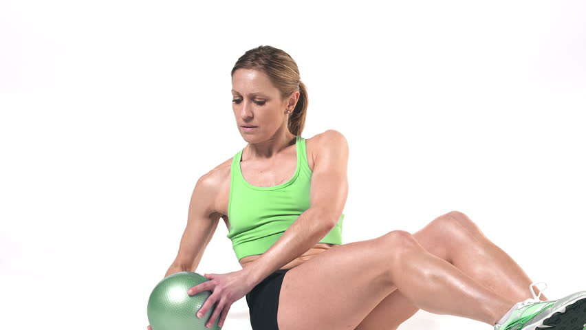 Wide Shot Of A Female Doing Ab Work Outs With Medicine Ball On White Background While Looking Into The Camera
