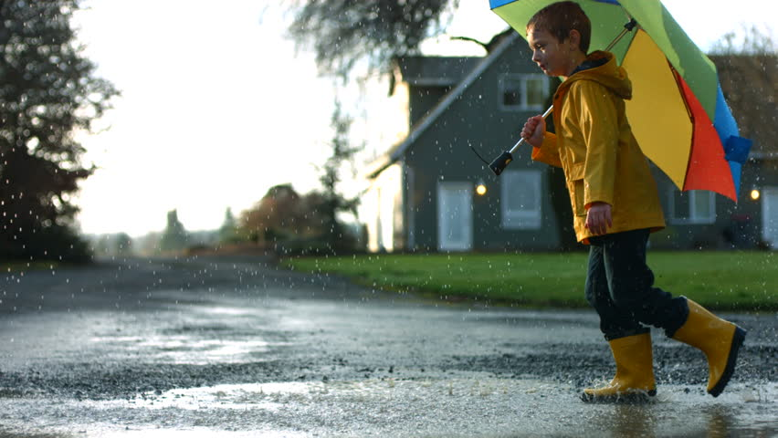 Young boy running through puddles with umbrella, slow motion #4627571