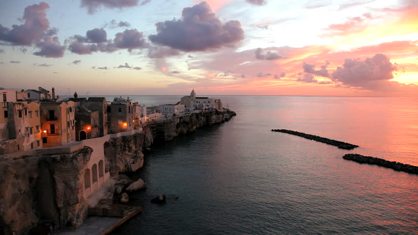 View of the beautiful scenic town of Vieste town jutting out in to the Adriatic Sea on a rocky promontory at sunrise in Puglia, Italy