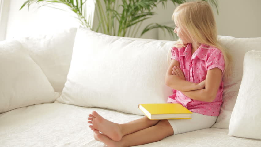 Cute little girl sitting on sofa with book and smiling at camera