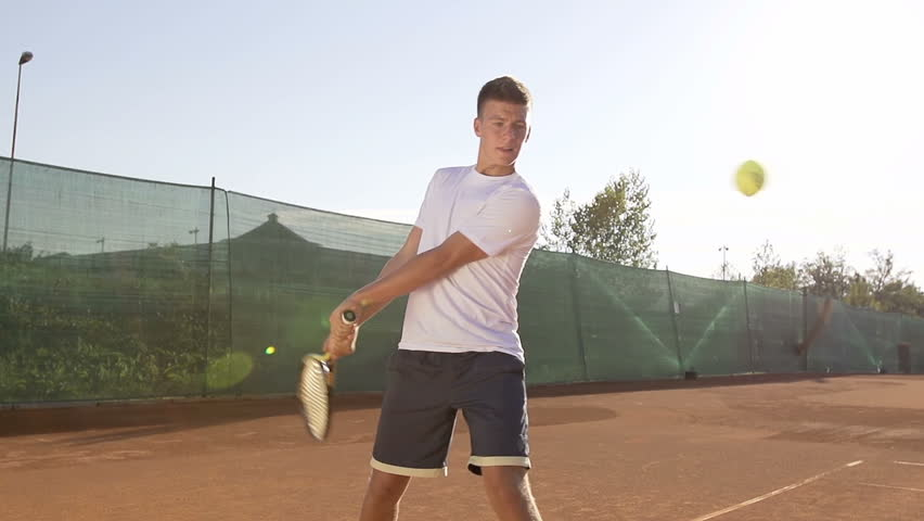 Slow Motion Shot Of A Young Professional Tennis Player Hitting Tennis Ball With