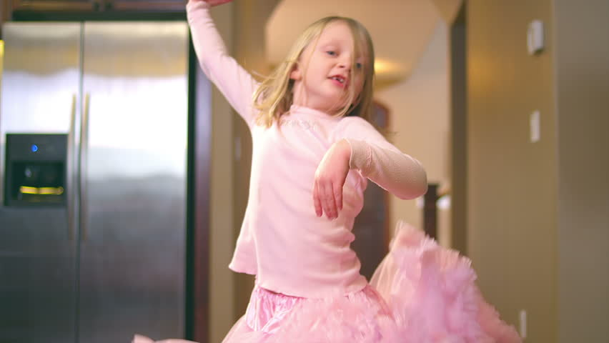 A cute girl is in her ballet uniform dancing around in the kitchen. Medium slow motion shot.