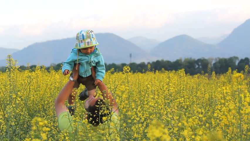 Young father play with happy smiling baby boy in the nature, hold in arms and raise up his child upon a yellow flowered rape spring field near mountains, having fun together