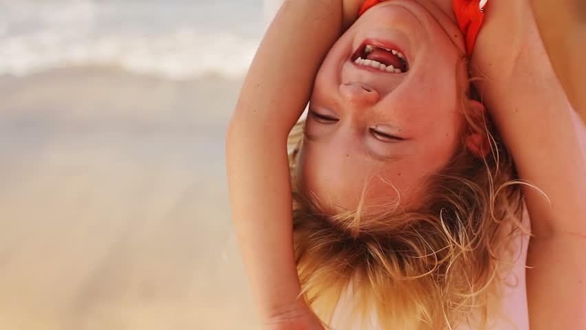 Little girl on her dad's shoulders gets tickled by her mom. Medium shot.