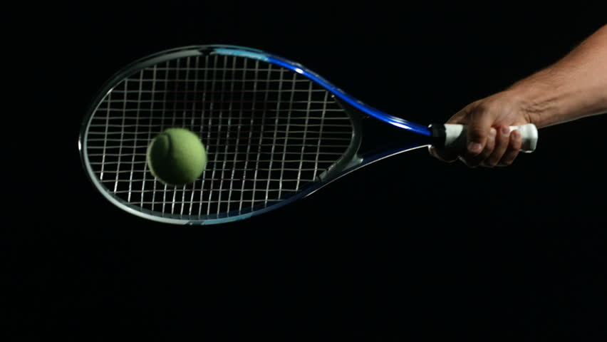 Tennis Ball being hit in slow motion against black background