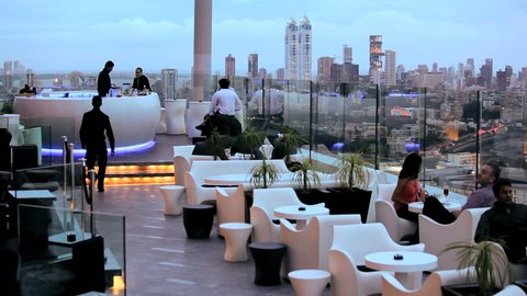 India - January 2011: People drinking and relaxing at a rooftop bar and restaurant with panoramic views of the skyline in Mumbai, India in January, 2011