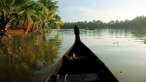Local canoes passing on the Kerala river backwater naear Alleppey, India