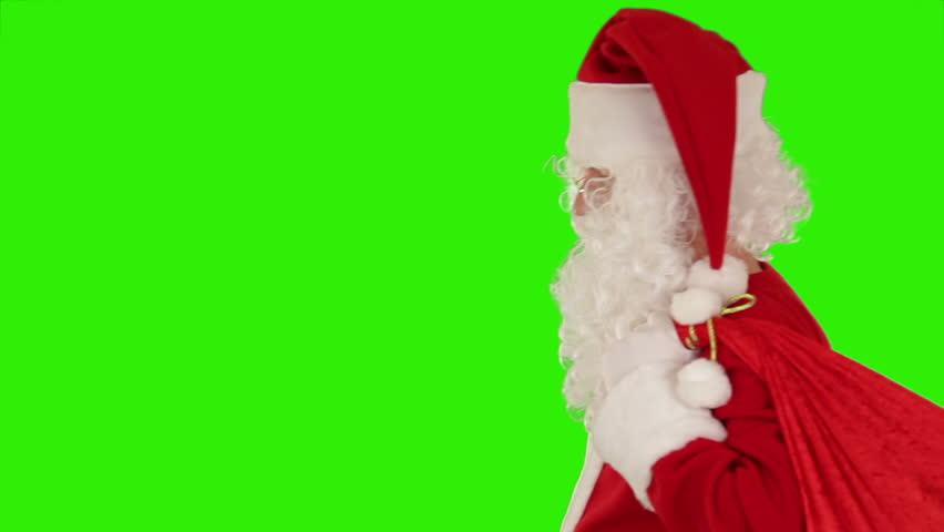 Santa Claus carrying his bag, is looking at camera, sends a kiss and wave, Green